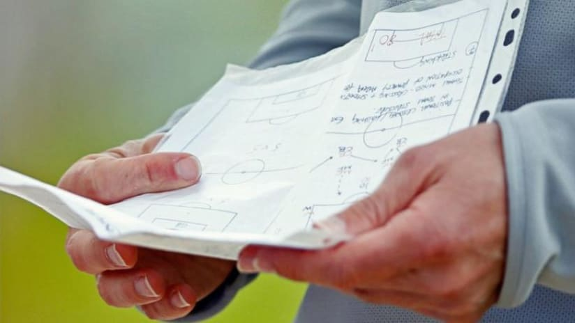 Coaching holding paper - scouting - tactics