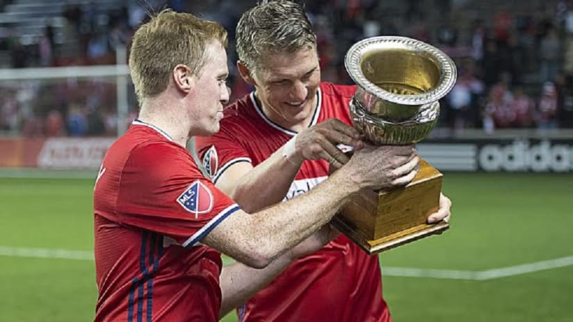 Bastian Schweinsteiger and Dax McCarty hold the Brimstone Cup