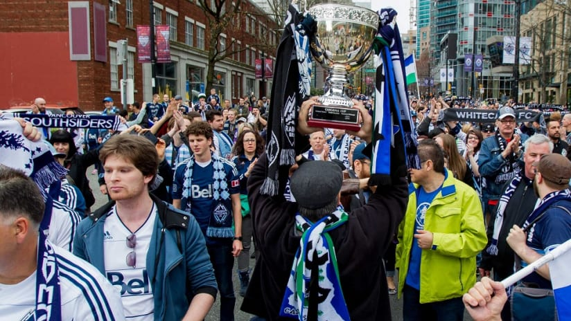 Vancouver Whitecaps supporters lift the Cascadia Cup while marching to CenturyLink Field