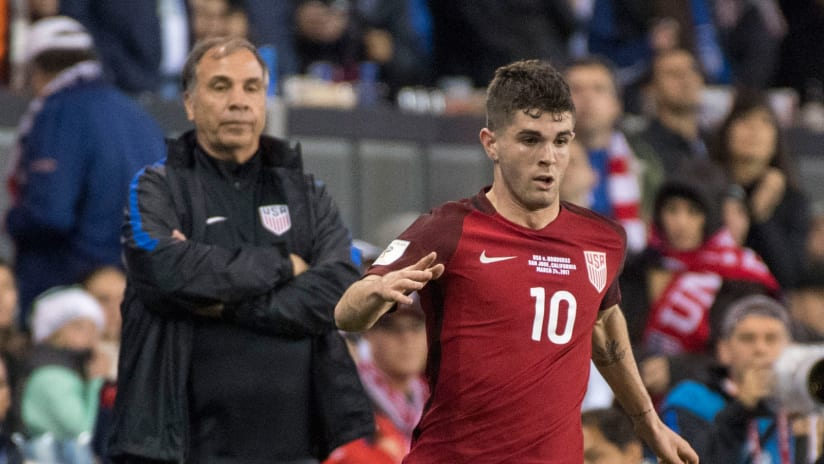Christian Pulisic dribbles while Bruce Arena looks on