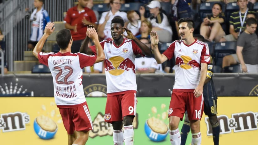 Anatole Abang of the New York Red Bulls is congratulated by Karl Ouimette and Sacha Kljestan