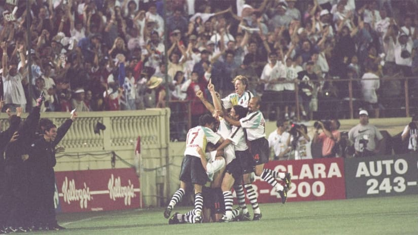 "Eric Wynalda is mobbed by his teammates after scoring the game-winning goal in the San Jose Clash's 1-0 victory against D.C. United in MLS' inaugural match. The match was scoreless until the 87th minute and fears that it would end without a goal prompted then MLS deputy commissioner and current U.S. Soccer Federation president Sunil Gulati to utter these famous words: ""Thank God for Eric Wynalda."""