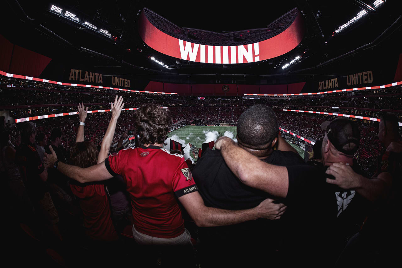 Supporters embrace each other after Atlanta United wins the match against Orlando City at Mercedes-Benz Stadium in Atlanta, Georgia on Friday September 10, 2021. (Photo by AJ Reynolds/Atlanta United)
